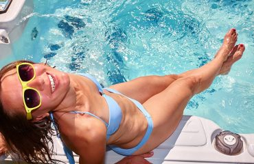 a smiling woman dipping her feet into a hot tub