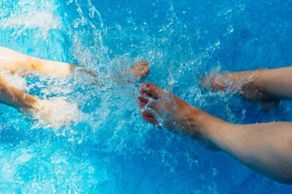 Man and woman's feet kicking and splashing in a hot tub.
