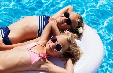 Two little girls on a float in a hot tub.
